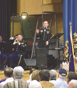 "Spc. Lawrence Evans, senior producer for the 1st Infantry Division Band, sings ""It's Beginning to Look a Lot like Christmas"" at the Pearl Harbor Day concert Dec. 7 at the Peace Memorial Auditorium in Manhattan, Kansas."