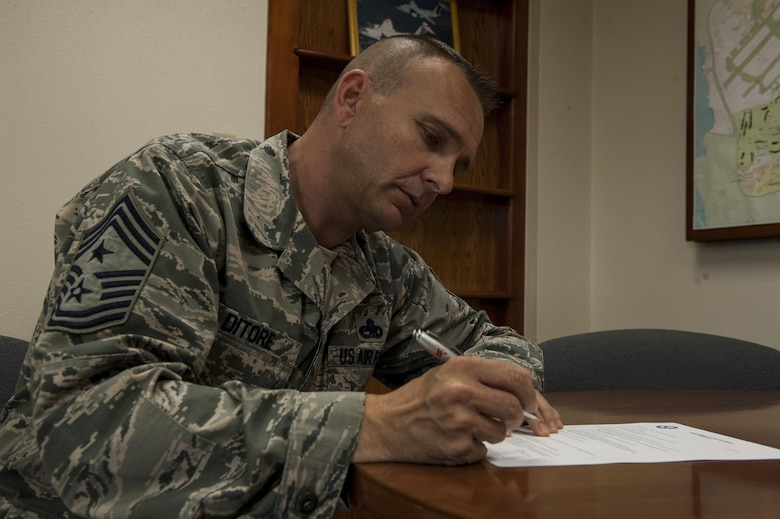 U.S. Air Force Chief Master Sgt. Michael Ditore, 18th Wing command chief, signs Senior Airman Below-The-Zone paperwork Dec. 13, 2016, at Kadena Air Base, Japan. Ditore makes Airmen his top priority as Kadena's newest senior enlisted leader; building relationships and making differences in lives has been a goal of Ditore's since his first day in the Air Force. (U.S. Air Force photo by Senior Airman Lynette M. Rolen/Released)