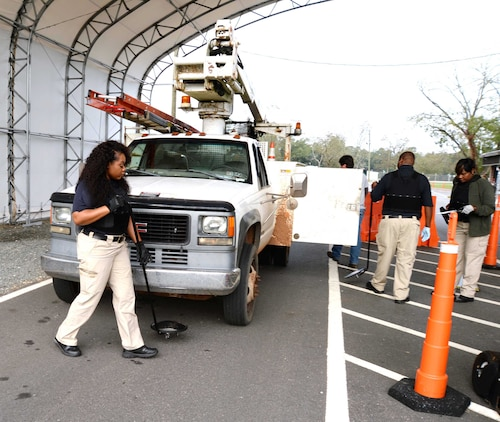 Members of the physical security team, at Marine Corps Logistics Base Albany, inspect a vehicle at the commercial truck entrance at Mock Road. According to the installation's security officials, the physical security team, assisted by military working dogs, inspect between 100-200 commercial vehicles every day.