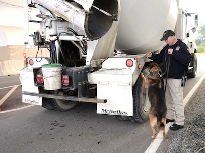 Cpl. Erin Zupko, police officer/K-9 handler, Marine Corps Police Department, Marine Corps Logistics Base Albany, and his military working dog, inspect a commercial vehicle as part of a routine security check at the Mock Road Commercial Truck Gate. All vehicles entering the installation are required to go through rigorous security protocols before access is granted.