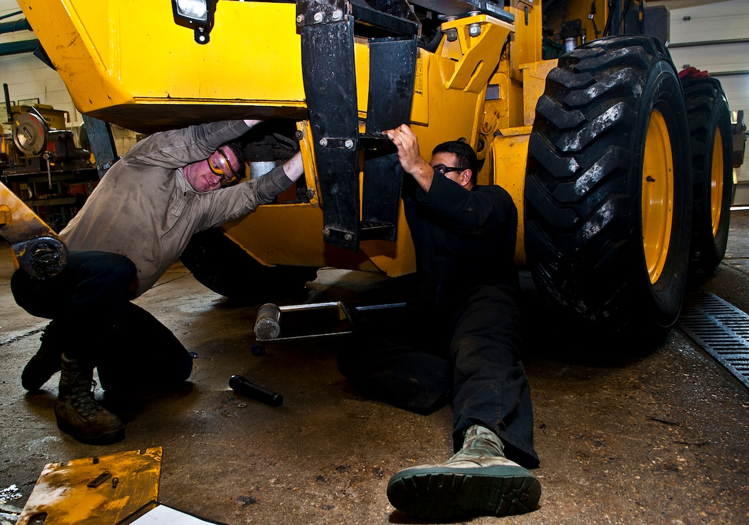 (From left) Airmen 1st Class Brennan Walley and Rodrigo Salgado, 5th Logistics Readiness Squadron vehicle maintenance technicians, install hydraulic lines on a grader vehicle at Minot Air Force Base, N.D., Dec. 14, 2016. These Airmen work on various components of government vehicles, such as electrical systems, brakes, transmissions, and heating and cooling systems. (U.S. Air Force photo/Airman 1st Class Jonathan McElderry)