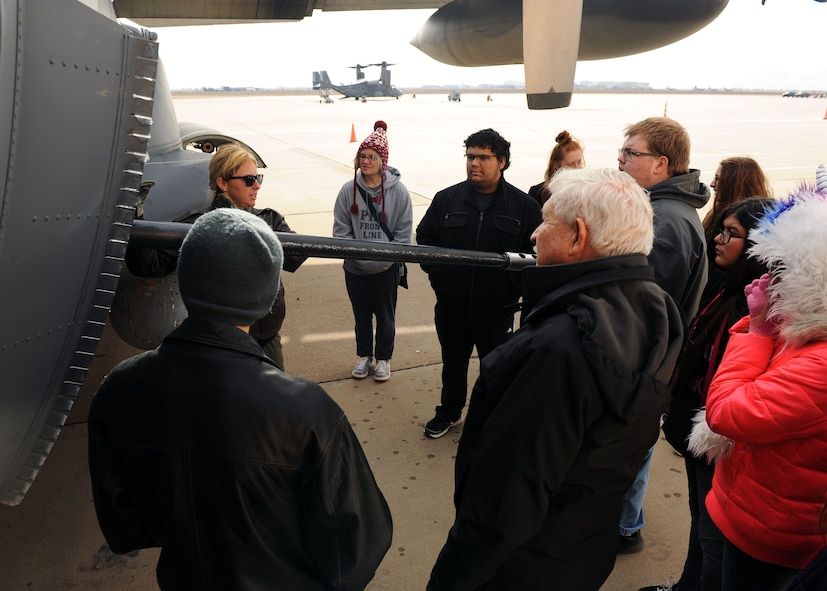 Capt. Katie Schuler, 16th Special Operations Squadron pilot, talks about AC-130W gunship capabilities during a tour for Portales High School Math Engineering and Science Achievement club members, Dec. 9, 2016, at Cannon Air Force Base, N.M. The tour, which consisted of an AC-130 technology brief and an in-depth look at a powered-on AC-130W, was designed to give students a practical look at real world math, engineering and science applications. (U.S. Air Force photo by Staff Sgt. Whitney Amstutz/Released)