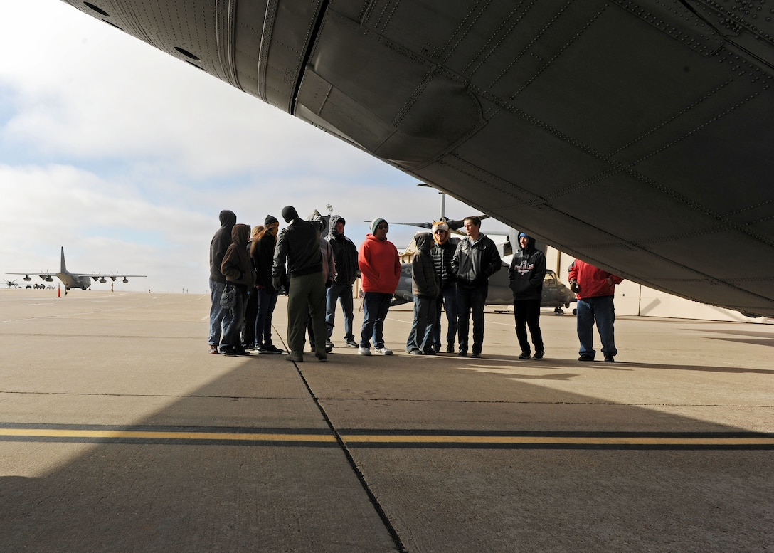 Capt. Daniel Sickles, 16th Special Operations Squadron Combat Systems officer, speaks to Portales High School Math Engineering and Science Achievement club members about the capabilities of an AC-130W, Dec. 9, 2016, during a tour at Cannon Air Force Base, N.M. The tour, which consisted of an AC-130 technology brief and an in-depth look at a powered-on AC-130W, was designed to give students a practical look at real world math, engineering and science applications. (U.S. Air Force photo by Staff Sgt. Whitney Amstutz/Released)