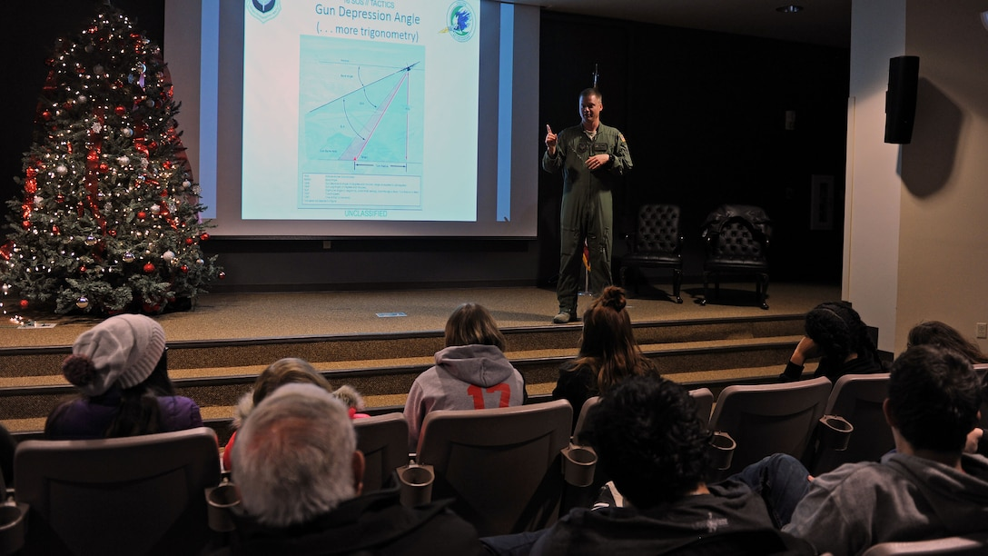 Capt. Daniel Sickles, 16th Special Operations Squadron Combat Systems officer, speaks to Portales High School Math Engineering and Science Achievement club members, Dec. 9, 2016, during a tour at Cannon Air Force Base, N.M. The tour, which consisted of an AC-130 technology brief and an in-depth look at a powered-on AC-130W, was designed to give students a practical look at real world math, engineering and science applications. (U.S. Air Force photo by Staff Sgt. Whitney Amstutz/Released)