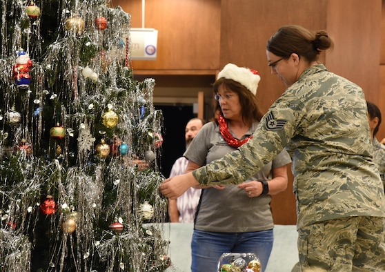 Barbara Walker, 335th Training Squadron training specialist, and Staff Sgt. Leanne Kirk, 81st Medical Group medical administrator, examine Christmas tree ornaments at the Armed Forces Retirement Home Dec. 29, 2016, Gulfport, Miss. Keesler Air Force Base personnel donated and delivered more than 66 gifts to residents at the home through the Adopt A Veteran program. (U.S. Air Force photo by Kemberly Groue)