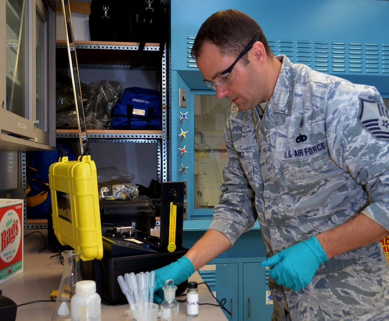 Master Sgt. Joe Runewicz, 111th Medical Group noncommissioned officer in charge of bioenvironmental engineering and occupational environmental health manager, illustrates the use of a machine to test solid samples at the 111th Attack Wing Medical Clinic, Horsham Air Guard Station, Pa., Dec. 22, 2016. The bioenvironmental engineering career field include various responsibilities, from the fetal protection program to occupational health hazard prevention. (U.S. Air National Guard photo by Tech. Sgt. Andria Allmond/Released)