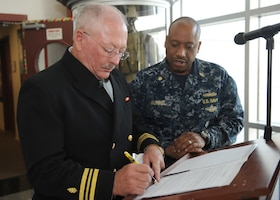 Navy Lt. Cmdr. Charles Wallace, left, signs his commissioning paperwork with Navy Lt. Cmdr. Markeece Murriel, health care administrator at Navy Recruiting Command in Millington, Tenn., Dec. 19, 2016. Following a 27-year career of private practice in plastic surgery, Wallace will now lend his medical expertise as part of the Navy Reserve. Navy photo by Petty Officer 3rd Class Brandon Martin