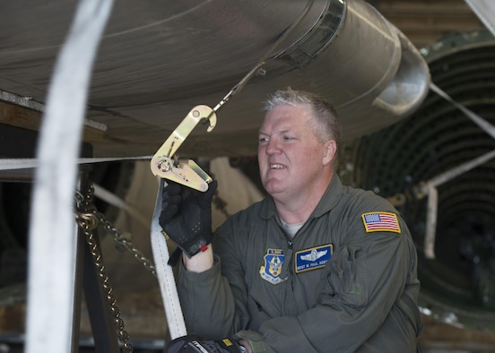"""Master Sgt. Paul Adkins, 709th Airlift Squadron loadmaster, straps down the wings of the Fairchild C-119B Flying Boxcar #48-0352 """"Am Can Co Special"""" inside a C-5M Super Galaxy Dec. 19, 2016, at Edwards Air Force Base, Calif. Adkins is an experienced loadmaster with more than 3,500 flight hours. (U.S. Air Force photo by Senior Airman Zachary Cacicia)"""