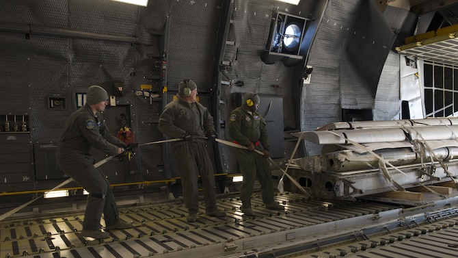 """Loadmasters from the 709th Airlift Squadron pull portions of the Fairchild C-119B Flying Boxcar #48-0352 """"Am Can Co Special"""" into the cargo bay of a C-5M Super Galaxy Dec. 19, 2016, at Edwards Air Force Base, Calif. This airlift mission was used as training experience for the new loadmasters. (U.S. Air Force photo by Senior Airman Zachary Cacicia)"""