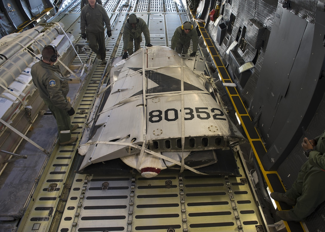 """Staff Sgt. Johnathan Barnes, 412th Logistics Readiness Squadron air transportation specialist, and Staff Sgt. Andrew Chilcoat, 412th LRS air transportation specialist, push the palletized tail section of the Fairchild C-119B Flying Boxcar #48-0352 """"Am Can Co Special"""" into a C-5M Super Galaxy's cargo bay Dec. 19, 2016, at Edwards Air Force Base, Calif. Barnes and Chilcoat, both stationed at Edwards AFB, were vital in logistic support of this mission. (U.S. Air Force photo by Senior Airman Zachary Cacicia)"""