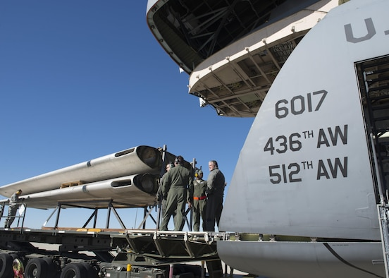 """Loadmasters from the 709th Airlift Squadron prepare to load the wings of the Fairchild C-119B Flying Boxcar #48-0352 """"Am Can Co Special"""" into a C-5M Super Galaxy Dec. 19, 2016, at Edwards Air Force Base, Calif. The wings were the only portions of the C-119 to be loaded through the C-5M's forward ramp. (U.S. Air Force photo by Senior Airman Zachary Cacicia)"""
