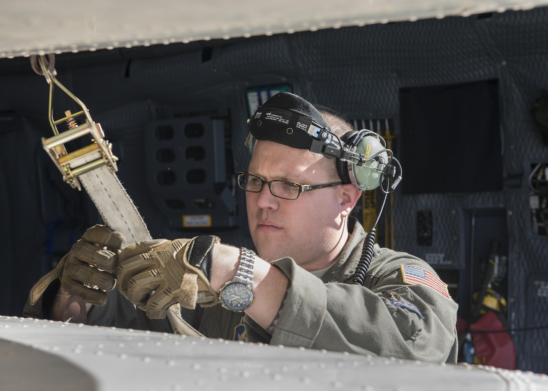 """Master Sgt. Bryan Muise, 709th Airlift Squadron loadmaster, straps down the wings of the Fairchild C-119B Flying Boxcar #48-0352 """"Am Can Co Special"""" inside a C-5M Super Galaxy Dec. 19, 2016, at Edwards Air Force Base, Calif. This C-119 was destined to be sold for scrap metal had it not been rescued by the Air Mobility Command Museum. (U.S. Air Force photo by Senior Airman Zachary Cacicia)"""
