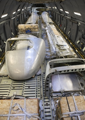 """Portions of the Fairchild C-119B Flying Boxcar #48-0352 """"Am Can Co Special"""" sit inside a C-5M Super Galaxy's cargo bay during a mission to bring it to the Air Mobility Command Museum Dec. 19, 2016, at Edwards Air Force Base, Calif. These aircraft portions weighed around 23,000 pounds. (U.S. Air Force photo by Senior Airman Zachary Cacicia)"""