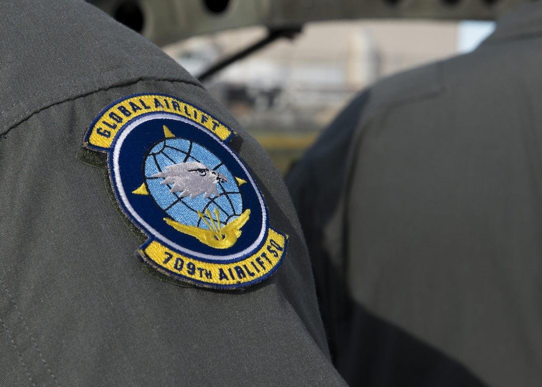 """A 709th Airlift Squadron patch sits on the shoulder of Master Sgt. Paul Adkins, 709th AS loadmaster, during a mission to bring the Fairchild C-119B Flying Boxcar #48-0352 """"Am Can Co Special"""" to the Air Mobility Command Museum via a C-5M Super Galaxy airlifter Dec. 16, 2016, at Edwards Air Force Base, Calif. The 709th AS is a component of the 512th Airlift Wing, a Reserve unit stationed at Dover AFB, Del. (U.S. Air Force photo by Senior Airman Zachary Cacicia)"""