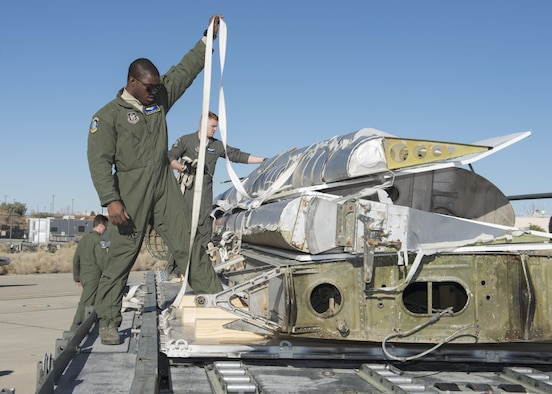"""Staff Sgt. Martin Guy, 709th Airlift Squadron loadmaster, straps down portions of the Fairchild C-119B Flying Boxcar #48-0352 """"Am Can Co Special"""" to a pallet during a mission to bring it to the AMC Museum via a C-5M Super Galaxy airlifter Dec. 17, 2016, at Edwards Air Force Base, Calif. Restoration work on the C-119 will take a minimum of two years. (U.S. Air Force photo by Senior Airman Zachary Cacicia)"""