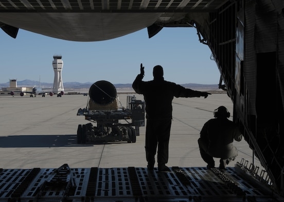 """Master Sgt. Paul Adkins, 709th Airlift Squadron loadmaster, and Master Sgt. Bryan Muise, 709th AS loadmaster, martial a K-Loader, carrying a tail-boom from the Fairchild C-119B Flying Boxcar #48-0352 """"Am Can Co Special,"""" toward the rear-cargo entrance of a C-5M Super Galaxy Dec. 19, 2016, at Edwards Air Force Base, Calif. This C-119 will be arguably the most historic aircraft in the Air Mobility Command Museum's collection. (U.S. Air Force photo by Senior Airman Zachary Cacicia)"""