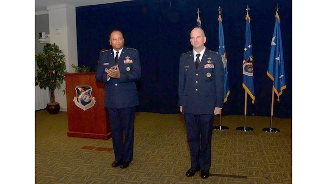 Lt. Gen. Samuel Greaves, commander of the Space and Missile Systems Center, and program executive officer for Space leads the audience in applauding Col. Dennis Bythewood, who assumed command of the Remote Sensing Systems Directorate Dec. 19, during a change of leadership ceremony in the Gordon Conference Center of the Schriever Space Complex at Los Angeles Air Force Base in El Segundo, Calif. (U.S. Air Force photo/Van De Ha)