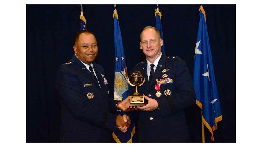 Lt. Gen. Samuel Greaves, commander of the Space and Missile Systems Center, and program executive officer for Space presents Brig. Gen. Michael Guetlein with a miniature replica of the SMC Armillary sculpture in recognition of his leadership at the center Dec. 19, during a change of leadership ceremony in the Gordon Conference Center of the Schriever Space Complex at Los Angeles Air Force Base in El Segundo, Calif.  General Guetlein, the departing Senior Material Leader of the RS Directorate, leaves SMC to become the program executive for programs and integration at the Missile Defense Agency in Huntsville, Alabama. (U.S. Air Force photo/Van De Ha)