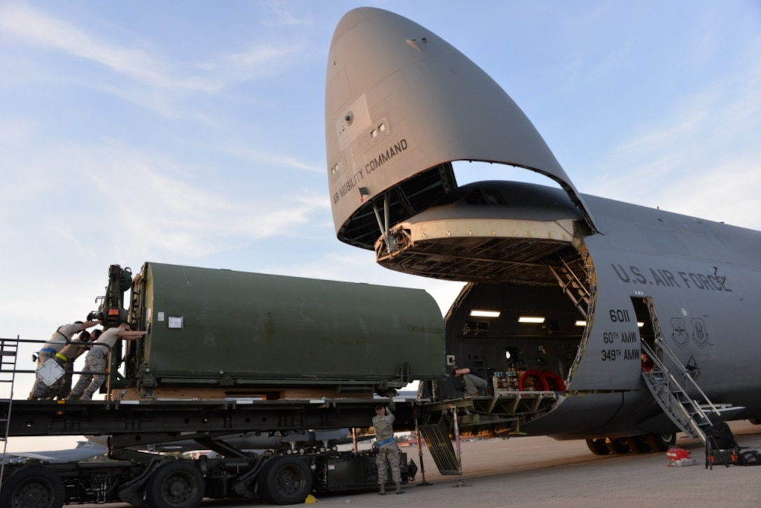 Airmen from the 60th Aerial Port Squadron load a C-5M Super Galaxy with essential cargo and an Improved Ribbon Bridge, May 12, 2016, at Travis Air Force Base, Calif. The bridge and cargo were flown to Iraq by the 22nd Airlift Squadron and directly contributed to the counter-Islamic State of Iraq and the Levant campaign during Operation Inherent Resolve in Mosul, Iraq. (U.S. Air Force photos by Senior Airman Amber Carter)