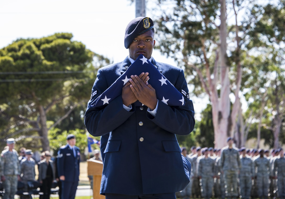 "Airman 1st Class Kelly Goodwin, 60th Security Forces Squadron, carries the American flag following a retreat ceremony at Travis Air Force Base, Calif., May 20, 2016. During the ceremony, the names of eight security forces and Air Force Office of Special Investigations Airmen were read aloud, signifying their ""end of watch."" (U.S. Air Force photo by Staff Sgt. Charles Rivezzo)"