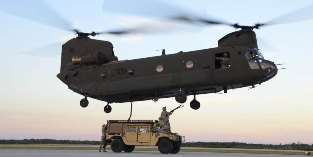 Airmen from the 821st Contingency Response Group out of Travis Air Force Base, California, get positioned to attach a HUMVEE to a U.S. Army CH-47 Chinook Aug. 9, 2016, at the Alpena Combat Readiness Training Center, Michigan, during Exercise Northern Strike. Exercise Northern Strike is a joint force exercise that combines the total force concept including Air Force, Army and Marines from various states and countries. (U.S. Air Force photo by Senior Airman Amber Carter)