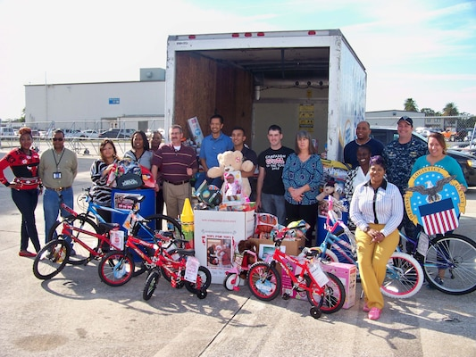 Employees from Defense Logistics Agency Aviation at Jacksonville, Florida pose with the toys they and Navy employees from Fleet Readiness Center Southeast's Avionics Shop collected for the annual Toys for Tots Program, December 12, 2016.