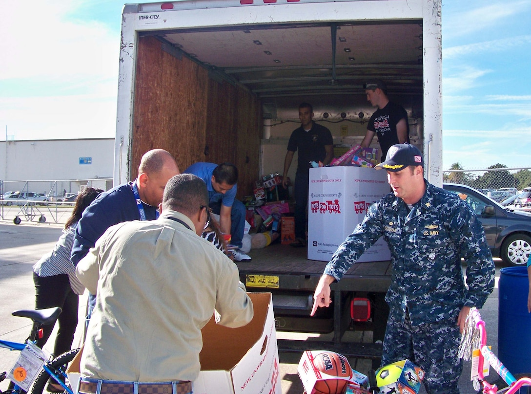 DLA Aviation at Jacksonville, Florida, Navy Commander Daniel Bessman, along with other DLA Aviation employees load boxes of toys and bicycles for the annual Toys for Tots Program Dec. 15, 2016.  DLA employees, along with Navy employees from Fleet Readiness Center Southeast's Avionics Shop, collected and donated six boxes of toys and 10 bicycles, which were given to families in need in the Greater Jacksonville area.
