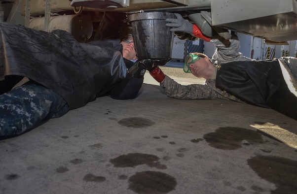 A member from the Naval Air Facility Atsugi Carrier Airborne Early Warning Squadron and an Airman with the 374th Logistics Readiness Squadron Fuels Management Flight hold a bucket to catch JP-8 fuel for an inspection at Yokota Air Base, Japan, Jan. 26, 2016. The Navy personnel who received training on the R-11 refueling trucks learned how to drive, service aircraft, perform minor maintenance and how to check fuel samples with the vehicle. (U.S. Air Force photo/Senior Airman David Owsianka)