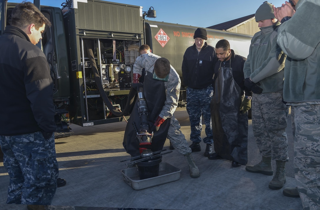 Senior Airman Tyler Sims, a 374th Logistics Readiness Squadron Fuels Management Flight fuels training supervisor, shows Sailors from Naval Air Facility Atsugi how to properly remove a fuel hose nozzle at Yokota Air Base, Japan, Jan. 26, 2016. The training allowed members to be prepared to support U.S. Navy aircraft at Andersen Air Force Base, Guam, during exercise Cope North. (U.S. Air Force photo/Senior Airman David Owsianka)