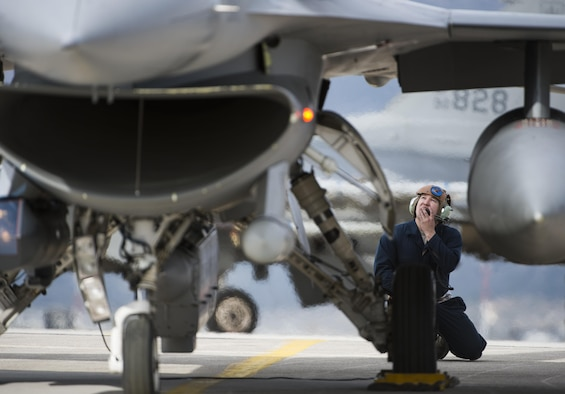 Staff Sgt. Ryan Anderson, a crew chief assigned to the 480th Expeditionary Fighter Squadron, performs preflight checks while communicating with a F-16 Fighting Falcon pilot before departure from the flightline at Souda Bay, Greece, Jan. 27. 2016. Anderson, along with 300 personnel from Spangdahlem Air Base, Germany, were participating in the flying training deployment between the Hellenic and U.S. air forces at Souda Bay from Jan. 22 to Feb. 15, 2016. (U.S. Air Force photo/Staff Sgt. Christopher Ruano)
