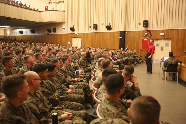 Motivational speaker Todd Parisi holds up his Spartan helmet for a war cry from Combat Logistics Regiment 25 at Camp Lejeune, N.C., Jan. 28, 2016. Parisi had promised a young girl battling leukemia that he would help keep her motivation high by recording a room full of Marines cheering for her. (U.S. Marine Corps photo by LCpl. Miranda Faughn/Released)