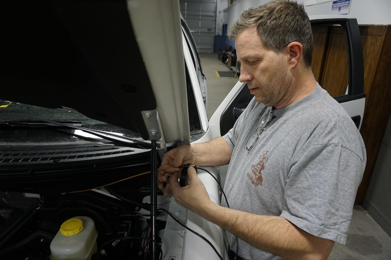 In this file photo dated Jan. 20, 2015, Sean Daugherty, 90th Communications Squadron electronic mechanic, wraps electrical tape over an exposed wire during the installation of new radio equipment in military owned vehicles on F.E. Warren Air Force Base, Wyo. The radio section, in which Daugherty works, maintains communications across the base and throughout its missile complex. (U.S. Air Force photo by Lan Kim)