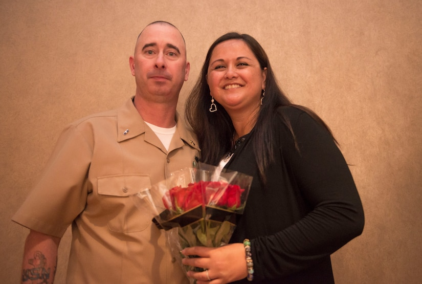 Former Master Chief Petty Officer Jason Roach stands with his wife, Judy, after presenting her roses  during his commissioning ceremony at the Red Bank Club on Joint Base Charleston – Naval Weapons Station, S.C., on Jan. 29, 2016. Roach was commissioned to CWO3 and his next duty station is aboard the USS Eisenhower, a nuclear-powered aircraft carrier. (U.S. Air Force photo/Airman 1st Class Thomas T. Charlton)