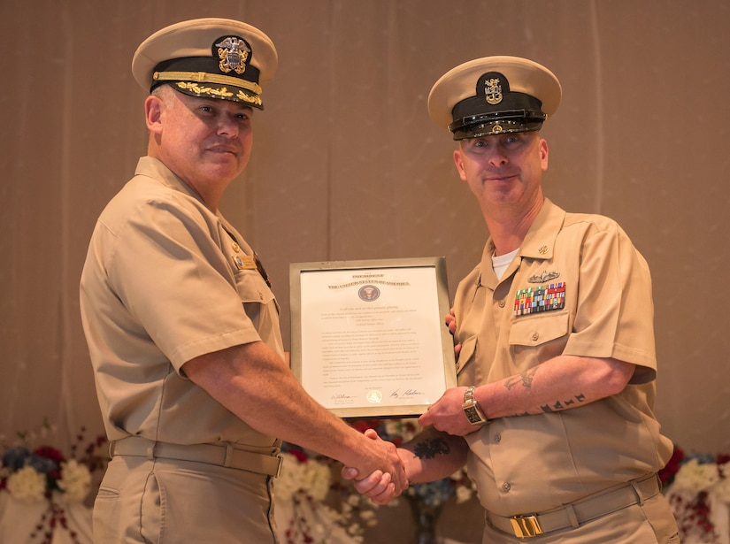 (From left to right) Navy Captain Charles Phillip, Naval Munitions Command Atlantic Unit Charleston commander, presents the document promoting former Master Chief Petty Officer Jason Roach to CWO3 at the Red Bank Club on Joint Base Charleston – Naval Weapons Station, S.C., on Jan. 29, 2016. Roach's next duty station is aboard the USS Eisenhower, a nuclear-powered aircraft carrier. (U.S. Air Force photo/Airman 1st Class Thomas T. Charlton)