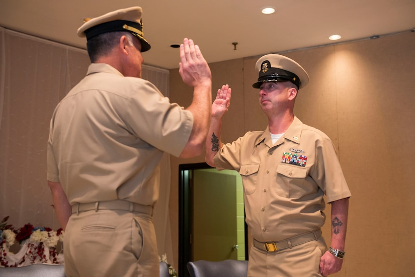 (From left to right) Navy Captain Charles Phillip, Navy Munitions Command Atlanta Unit Charleston commander, swears former MCPO Jason Roach in as a CWO3 during Roach's commissioning ceremony at the Red Bank Club on Joint Base Charleston – Naval Weapons Station, S.C., on Jan. 29, 2016. (U.S. Air Force photo/Airman 1st Class Thomas T. Charlton)