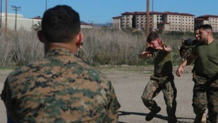 While under the blinding effect of oleoresin capsicum (OC) spray, Marines are led through an obstacle course by an instructor of a non-lethal weapons course, at Marine Corps Base Camp Pendleton, California, Jan. 26, 2016. During the course, Marines learned various techniques such as lower and upper body strikes and take-down control techniques. They also learned riot control and detainee handling. The Marines are with Company B, 1st Combat Engineer Battalion, 1st Marine Division, I Marine Expeditionary Force.