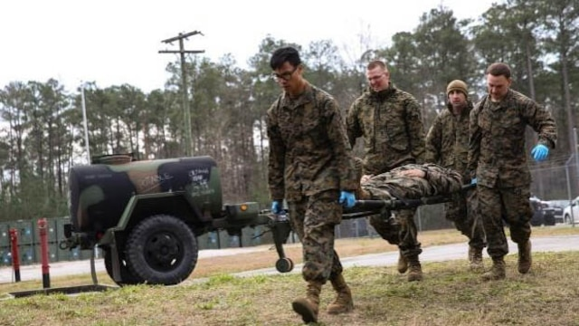 Corpsmen with 2nd Medical Battalion rush role-playing patients into a medical tent at Marine Corps Base Camp Lejeune, N.C, Jan. 28, 2016.  The training is preparing a Shock Trauma Squad to treat cold related injuries for an upcoming multinational exercise, Cold Response 16.1, in Norway.