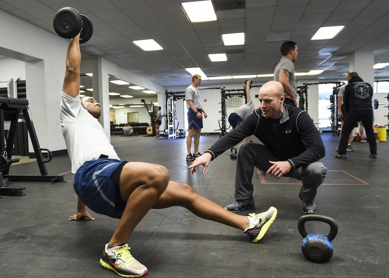 David Koch, an embedded athletic trainer with the 59th Medical Wing's VIPER Clinic, teaches Senior Airman Christopher Rodriguez, a student from the 342nd Training Squadron, proper lifting techniques, Jan. 27, 2016, at the Battle Gym on Joint Base San Antonio-Lackland, Texas. Four athletic trainers are working with students at the 342nd and 343rd Training Squadrons to determine the effectiveness of embedding athletic trainers into military physical training programs. If successful, the initiative could potentially reshape how injured trainees receive care. (U.S. Air Force photo/Staff Sgt. Michael Ellis)