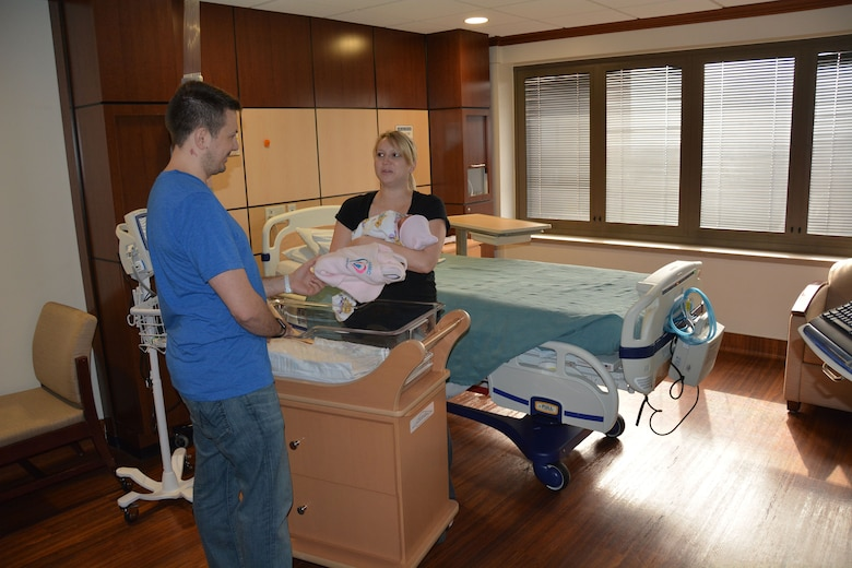 Maj. Nicholas Carr, a neonatologist, takes a break from his paternity leave to give Staff Sgt. Keri Sorsby a sleep sack for her newborn Isabella in the post-partum unit at San Antonio Military Medical Center, Jan. 25, 2016. SAMMC is partnering with Bexar County on the Safe to Sleep campaign, which encourages parents to place babies on their backs on a firm surface free of pillows, crib bumpers and loose bedding. Carr is with the 959th Medical Operations Squadron. (U.S. Army photo by Robert T. Shields/Released)
