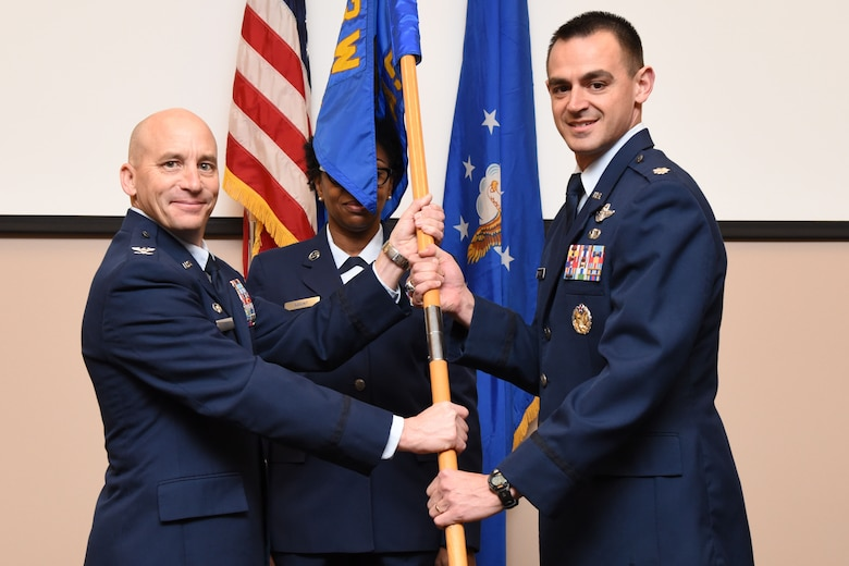 Col. David Condit, 403rd Operations Group commander, passes the 815th Airlift Squadron guide on to Lt. Col. Stuart Rubio, 815th AS commander, during a change of command ceremony January 30, 2016, at Keesler Air Force Base, Mississippi. Rubio took command of the 815th AS during the ceremony, which was held in the 815th AS building. (U.S. Air Force photo/Tech. Sgt. Ryan Labadens)