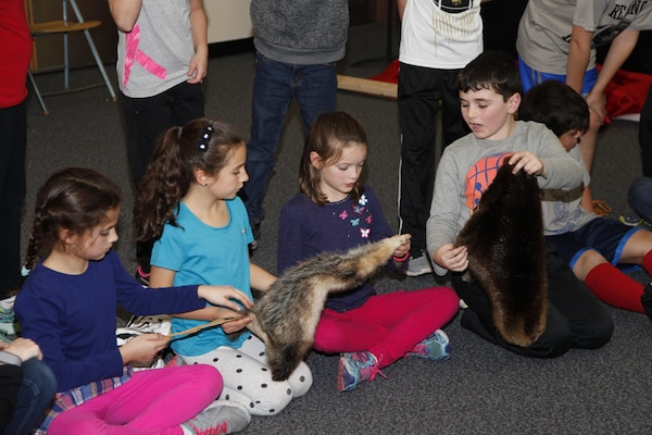 Students touch real animal pelts during the presentation.