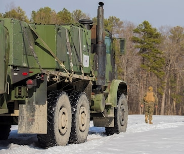 A Marine with Combat Logistics Battalion 2 ground guides a Medium Tactical Replacement vehicle at Fort A.P. Hill, Va., Jan. 29. During a two-week Deployment For Training exercise, a detachment of approximately 70 Marines provided support to 3rd Battalion, 2nd Marine Regiment, transferring gear and personnel in harsh winter conditions. The exercise allowed both battalions to work side by side and familiarize themselves with the organization of each other's units.