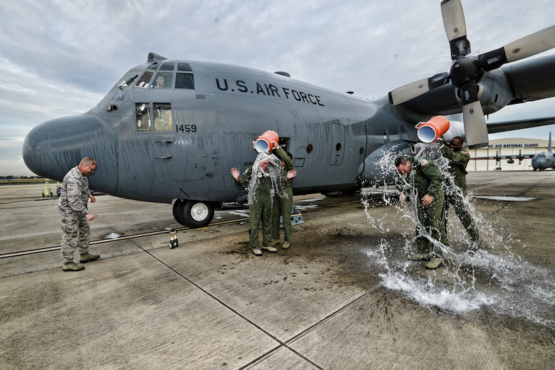 """In a longstanding military tradition, U.S. Air Force Master Sgt. Pennie Brawley (left) douses Vice Wing commander, Col. Quincy """"Newt"""" Huneycutt, III, with ice cold water as Senior Master Sgt. Jermaine Parker (right), does the same to Chief Master Sgt. Andrew """"Andy"""" Huneycutt after the brothers exit the 145th Airlift Wing, C-130 Hercules aircraft for the last time at the North Carolina Air National Guard Base, Charlotte Douglas International Airport. Combined, the brothers leave the 145th Airlift Wing with over 72 years of honorable military service. (U.S. Air National Guard photo by Staff Sgt. Yolanda Addison /Released)"""