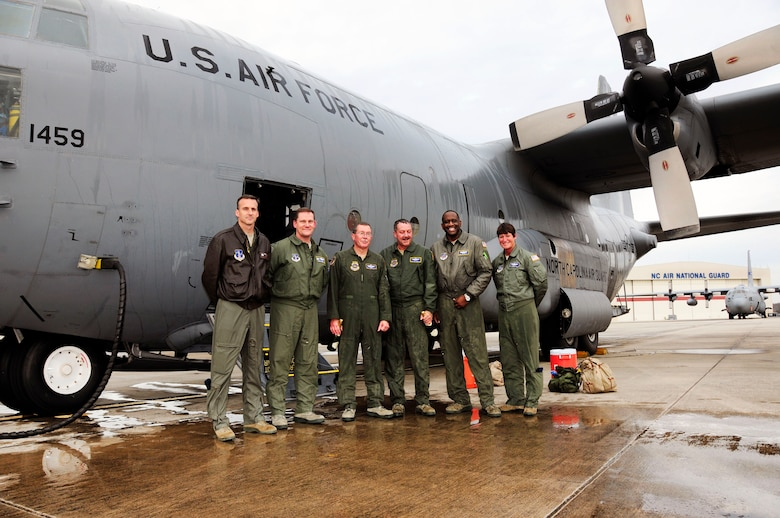 U.S. Air Force Col. Quincy Huneycutt, III, Vice Wing commander and navigator for the 145th Airlift Wing, alongside his brother, loadmaster, Chief Master Sgt. Andrew Huneycutt, (middle) stands with fellow aircrew Col. Jaye Stepp, commander ,Operations Group, Col. Kevin Harkey, commander, 156th Airlift Squadron,(right) and loadmasters, Senior Master Sgt. Jermaine Parker and Master Sgt. Pennie Brawley (right), after taking their final flight at the North Carolina Air National Guard Base, Charlotte Douglas International Airport; December 21, 2015. Combined, the brothers leave the 145th Airlift Wing with over 72 years of honorable military service. (U.S. Air National Guard photo by Master Sgt. Patricia F. Moran/Released)