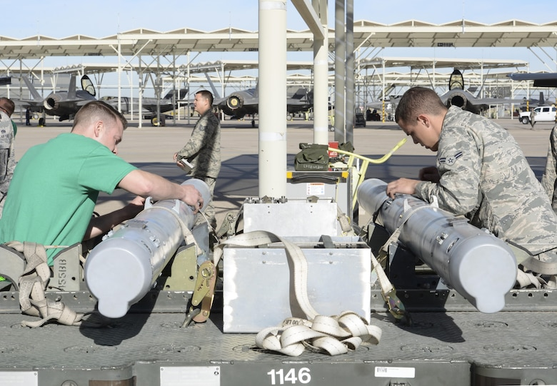 Load crew members from opposing teams race to prepare munitions for loading Jan. 29 during the 2015 Annual Load Crew Competition at Luke Air Force Base. Six load crew teams, including two from Holloman AFB, New Mexico, competed. The winner will be announced at the Maintenance Professional of the Year Banquet in March.