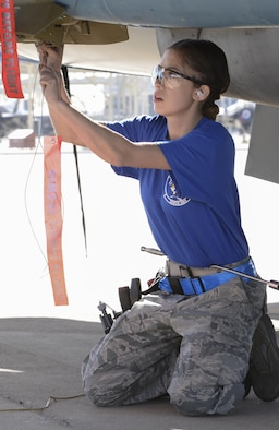 Airman 1st Class Nadiya Frick, 309th Aircraft Maintenance Unit load crew member, secures a weapon during the competition. Teams compete by racing to complete the loading of several weapons to their respective aircraft under the scrutiny of experienced judges.