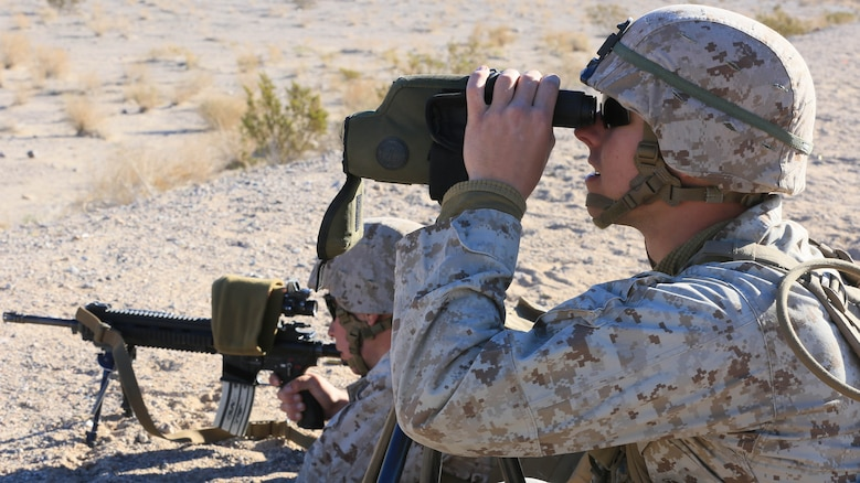 Pfc. Landon Heger, rifleman, 3rd Battalion, 7th Marine Regiment, spots targets for Pfc. Conner Price, rifleman, 3/7, during the Designated Marksman Course's culminating event at Range 113, Jan. 28, 2016. More than 10 'Cutting Edge' and 'Darkside' Marines in shooter-spotter teams participated in the three-week course utilizing the M27 Infantry Automatic Rifle.