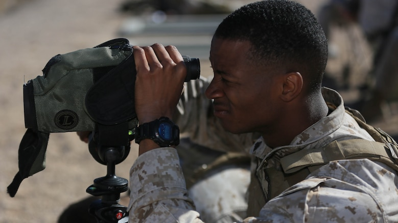 Corporal Robert Ellis, rifleman, 3rd Battalion, 4th Marines, 7th Marine Regiment, spots targets for his shooter during the Designated Marksman Course's culminating event at Range 113, Jan. 28, 2016. This is the first time a designated marksman course is being held aboard the Combat Center utilizing the Infantry Automatic Rifle.