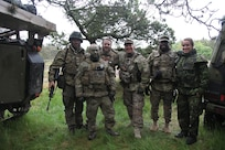 Danish army Soldiers stand next to U.S. Army Staff Sgt. Mark Korte, center, a civil affairs noncommissioned officer with Company B, 457th Civil Affairs Battalion, 361st Civil Affairs Brigade, 7th CSC and a native of El Cerrito, Calif., and U.S. Army Sgt. 1st Class Jerome Smith, a civil affairs NCO with Company B, 457th CA Battalion, 361st CA Brigade, 7th CSC and a native of Tampa, Fla., June 18, 2015 and their Danish interpreter during the Danish army's Civil Military Cooperation Support Team, 2nd Armored Infantry Battalion's NATO Response Force validation and training exercise Brave Lion 15, held June 8-19, 2015. (Photo by Sgt. 1st Class Matthew Chlosta, 7th CSC Public Affairs Office)