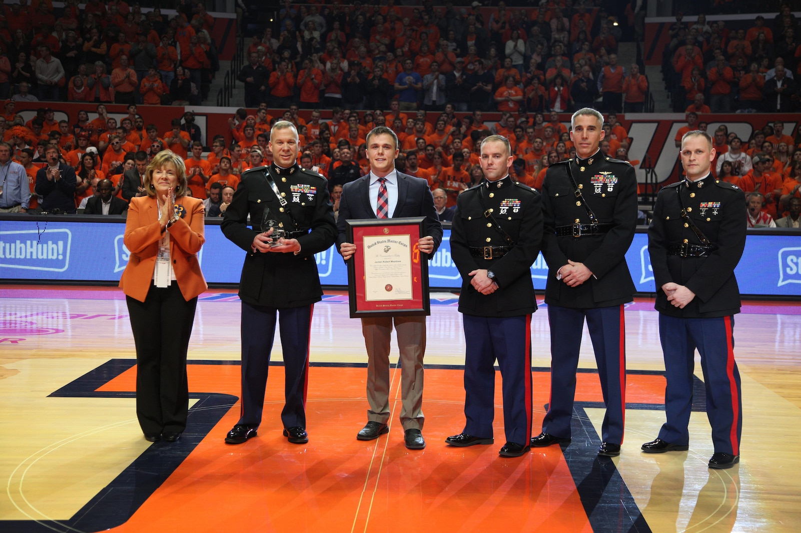 Jordan Meadows is presented the Commandant of the Marine Corps Trophy by members of Recruiting Station St. Louis Jan. 31 at the University of Illinois Basketball game for finishing top of his class of 220 Officer Candidates. Jordan's superb physical fitness, self-less leadership and successful academics distinguished him as the number one candidate.